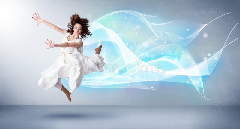 跳跃与抽象蓝色围巾的逗人喜爱的少年在她附近 库存图片