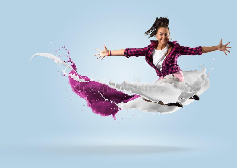 跳跃与油漆飞溅的年轻女性舞蹈家  免版税图库摄影