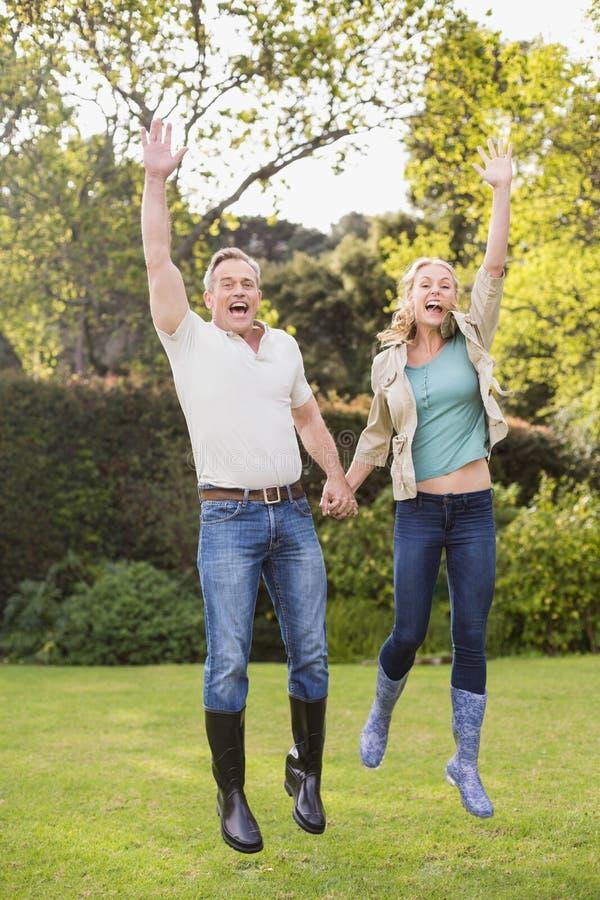 跳跃与胳膊的逗人喜爱的夫妇在天空中 免版税库存图片