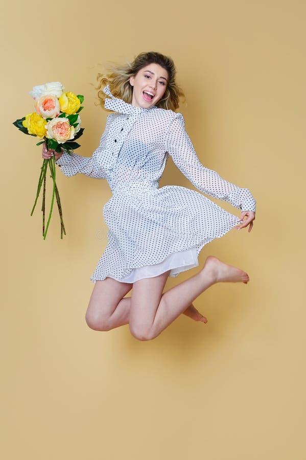 跳跃与花花束的快乐的妇女 库存照片