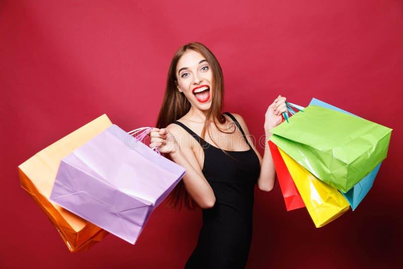 跳跃与许多购物袋的可爱的妇女 图库摄影