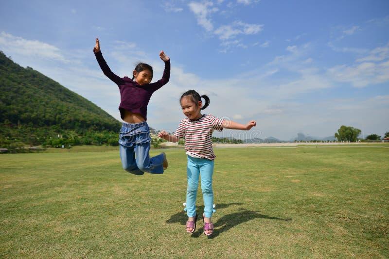 跳跃与绿草的愉快的亚洲孩子 免版税库存图片