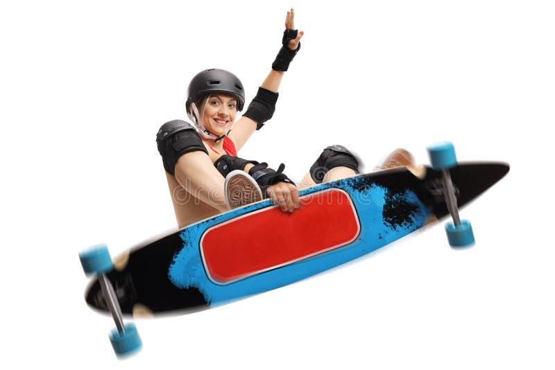 跳跃与longboard的年轻女性溜冰者 免版税库存图片