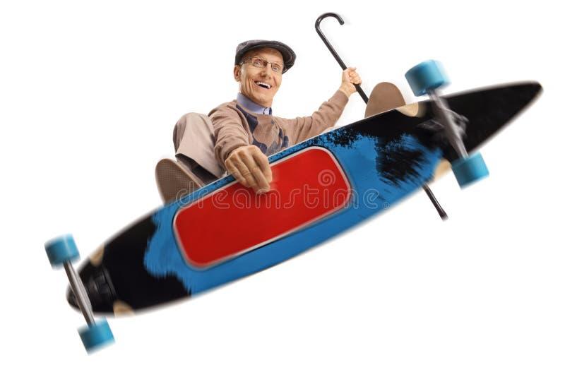 跳跃与longboard的年长人 免版税库存照片