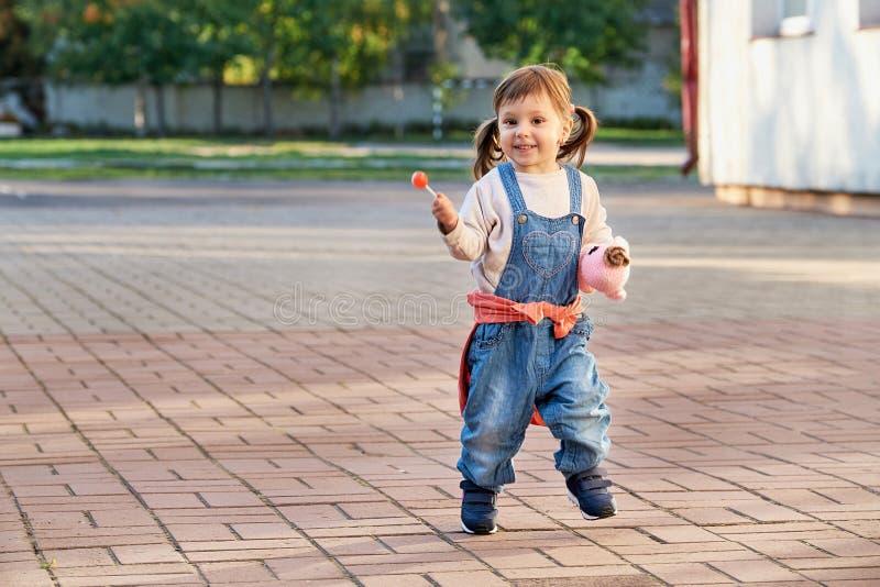 跳跃为喜悦的滑稽的小女孩 牛仔布总体的一个幼儿 免版税库存图片