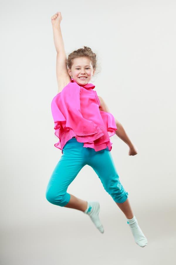跳跃为喜悦的激动的愉快的小女孩孩子 免版税库存照片