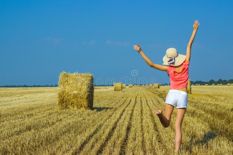 跳跃为喜悦的美丽的愉快的女孩在天空中在干草堆附近 免版税库存图片