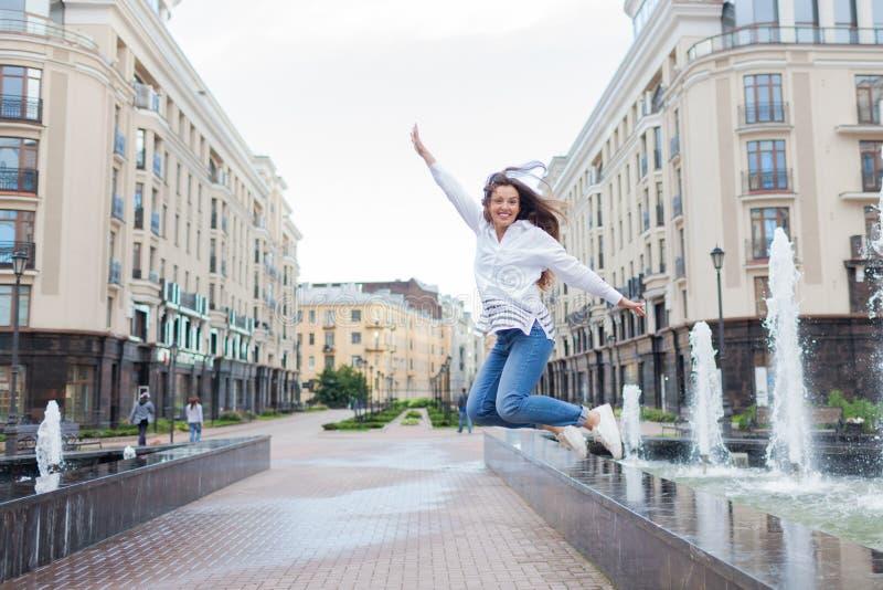 跳跃为喜悦的年轻运动的女孩在住宅复合体的喷泉 女性在飞行中用他的手 库存图片
