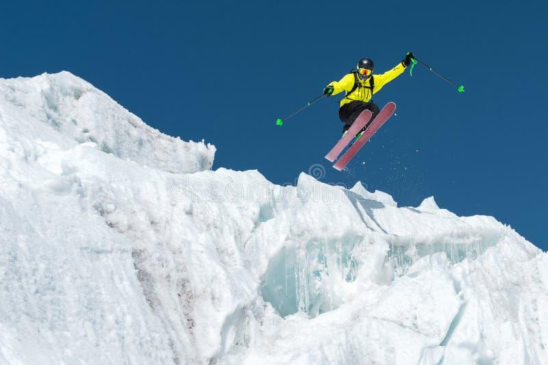 跳跃从冰川的一个跳跃的滑雪者反对蓝色高昂在山 专业滑雪 免版税库存照片