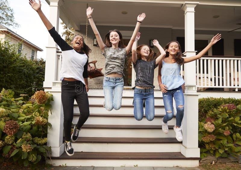 跳跃从房子的前面步的四个青少年女孩 免版税库存照片