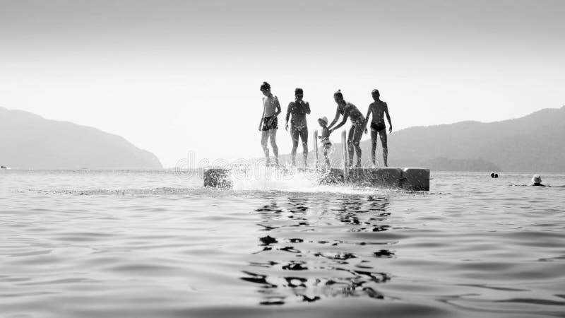 跳跃从浮方船的年轻人的黑白图象在风平浪静 库存照片