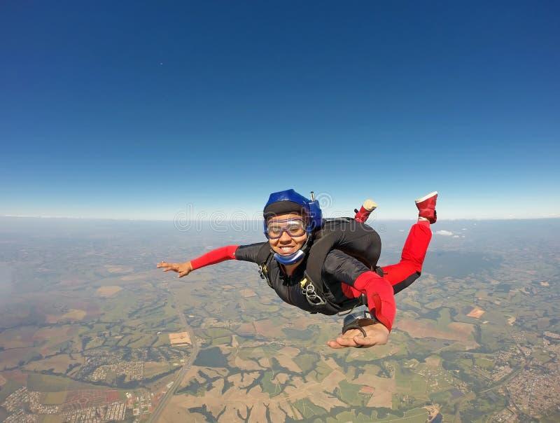 跳跃从降伞的微笑的黑人妇女 免版税库存照片