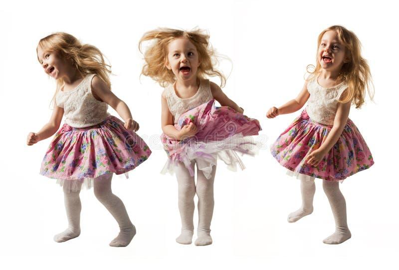 跳跃充满喜悦的逗人喜爱的小女孩隔绝在白色背景 库存图片