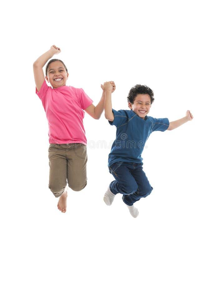 跳跃充满喜悦的活跃愉快的孩子 库存照片