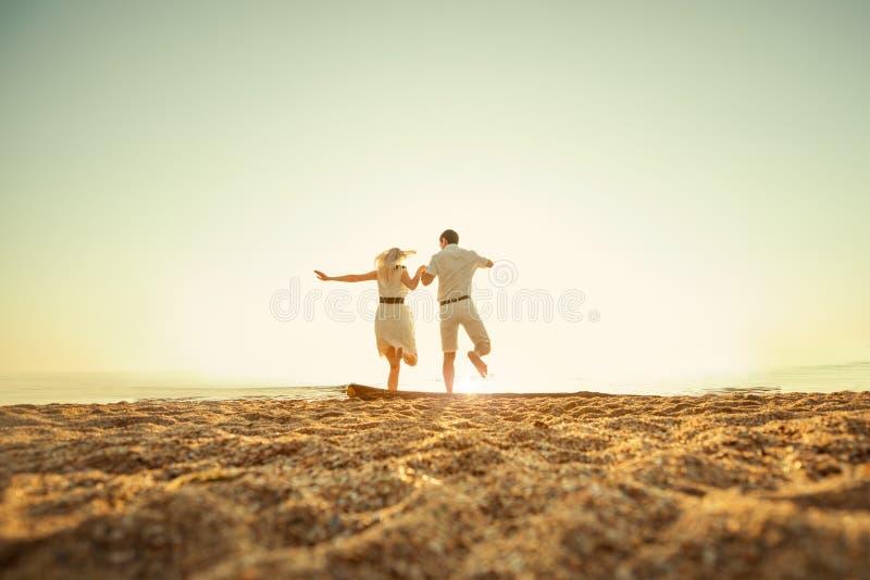 跳跃到海的夫妇 免版税图库摄影