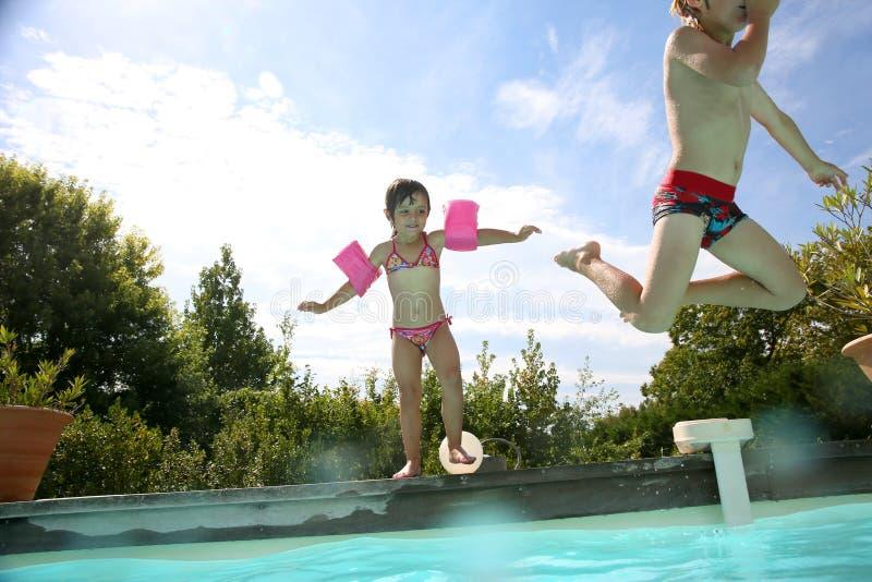 跳跃到游泳池的快乐的孩子 库存照片