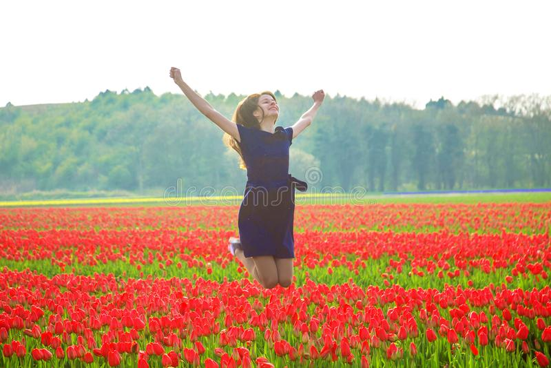 跳跃反对春天郁金香领域的愉快的青少年女孩 库存照片