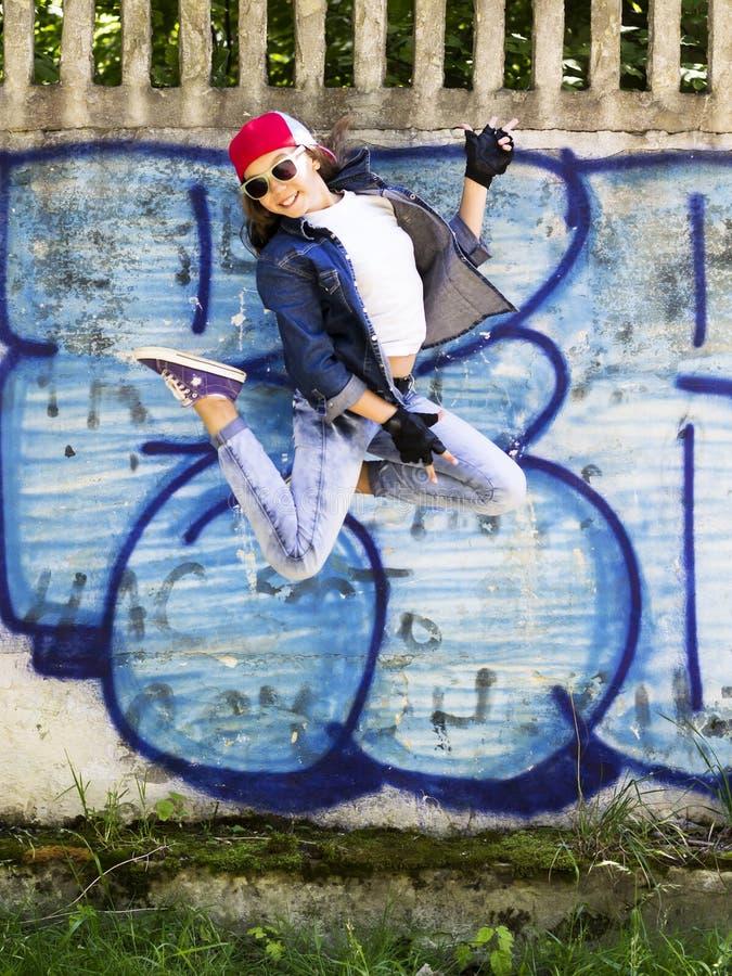 跳跃反对石墙背景的棒球帽和牛仔裤衬衣的逗人喜爱的年轻白肤金发的少年女孩 Hip Hop, 免版税图库摄影