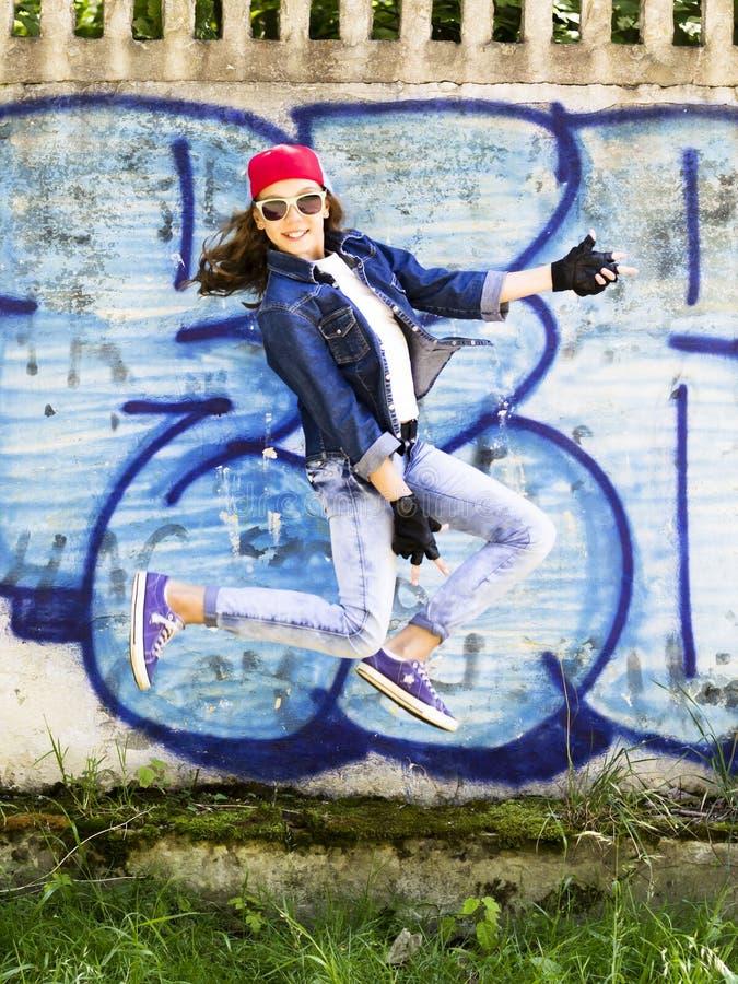 跳跃反对石墙背景的棒球帽和牛仔裤衬衣的逗人喜爱的年轻白肤金发的少年女孩 Hip Hop, 免版税库存图片