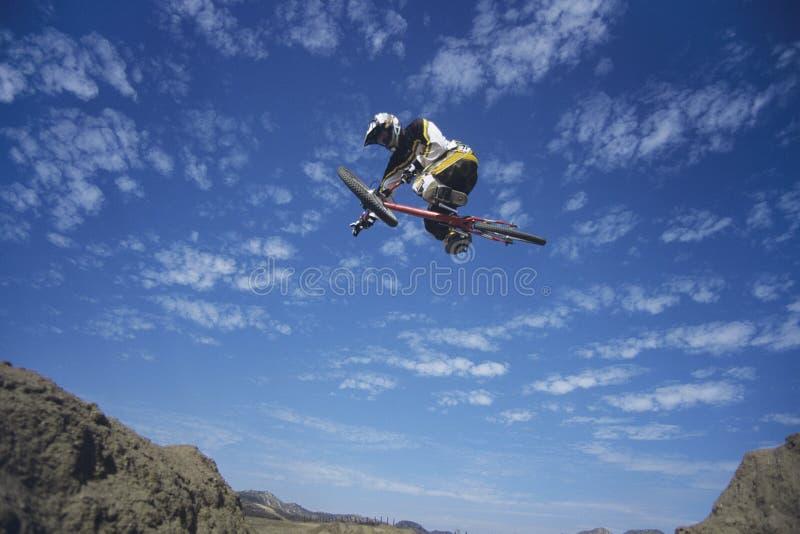跳跃反对蓝天的山骑自行车的人 免版税库存照片