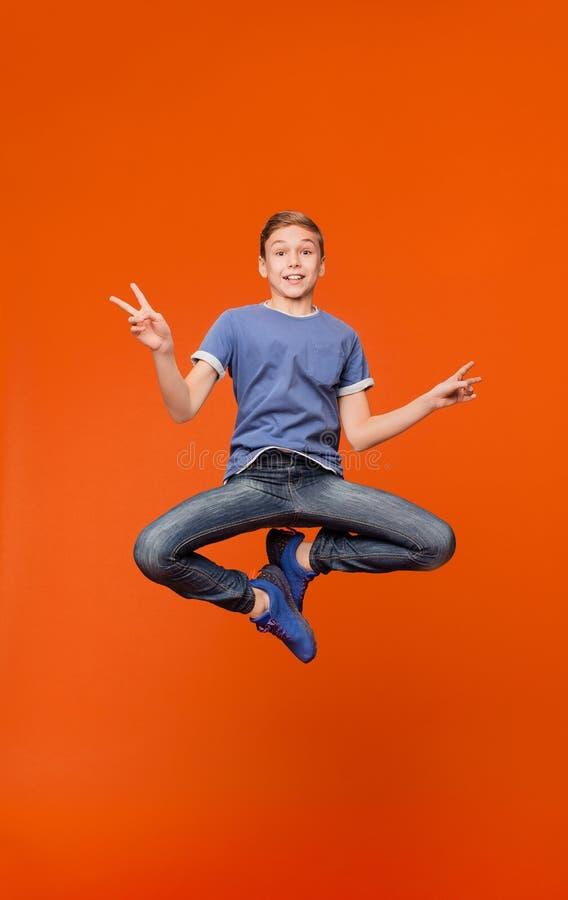 跳跃和打手势和平标志的逗人喜爱的男孩 图库摄影