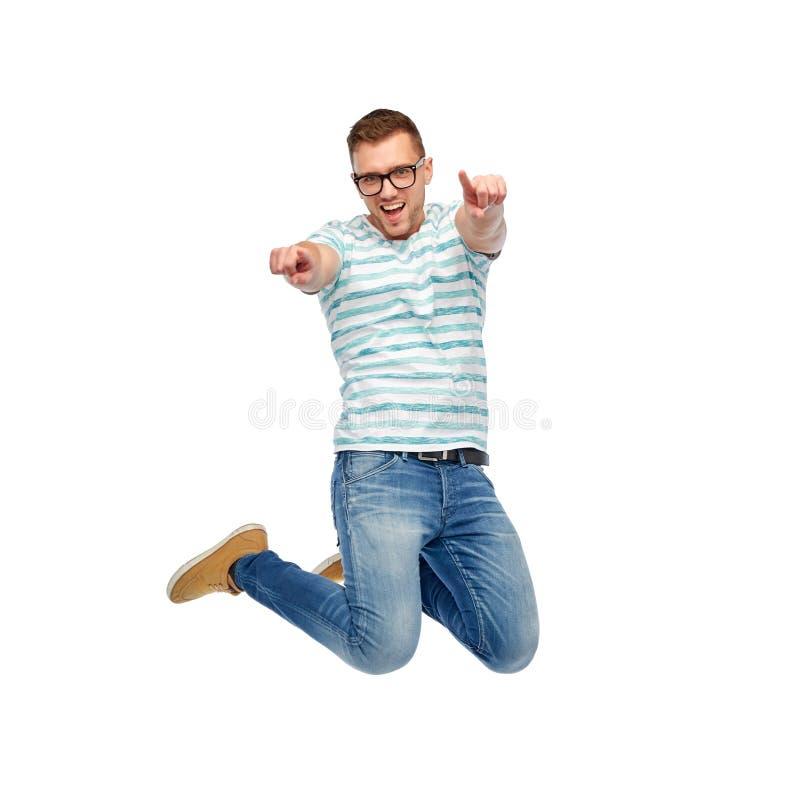 跳跃和指向手指的愉快的人您 库存图片
