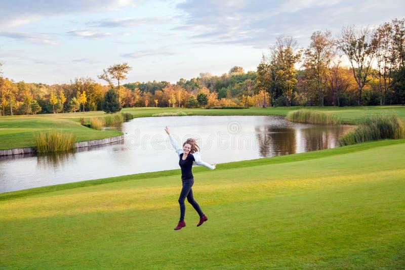 跳跃和跑在高尔夫球cou的绿草的逗人喜爱的女孩 库存照片