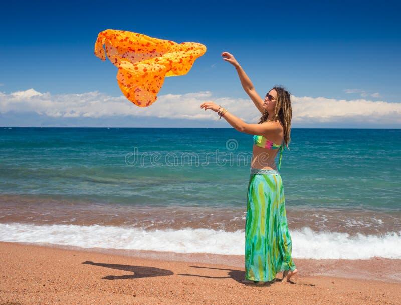 跳跃和跳舞海滩的愉快的女孩,适合在比基尼泳装,妇女的运动的健康性感的身体享用风,自由 免版税库存照片