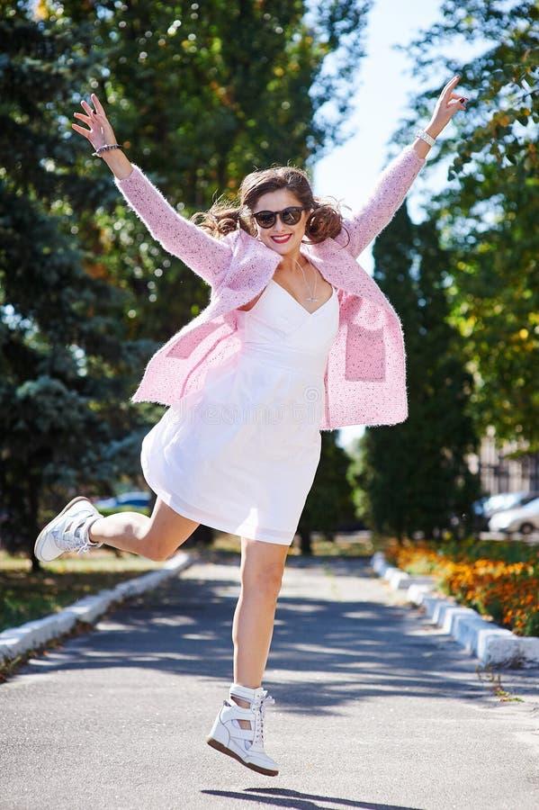 跳跃在充满喜悦的公园的玻璃的愉快的少妇 库存照片
