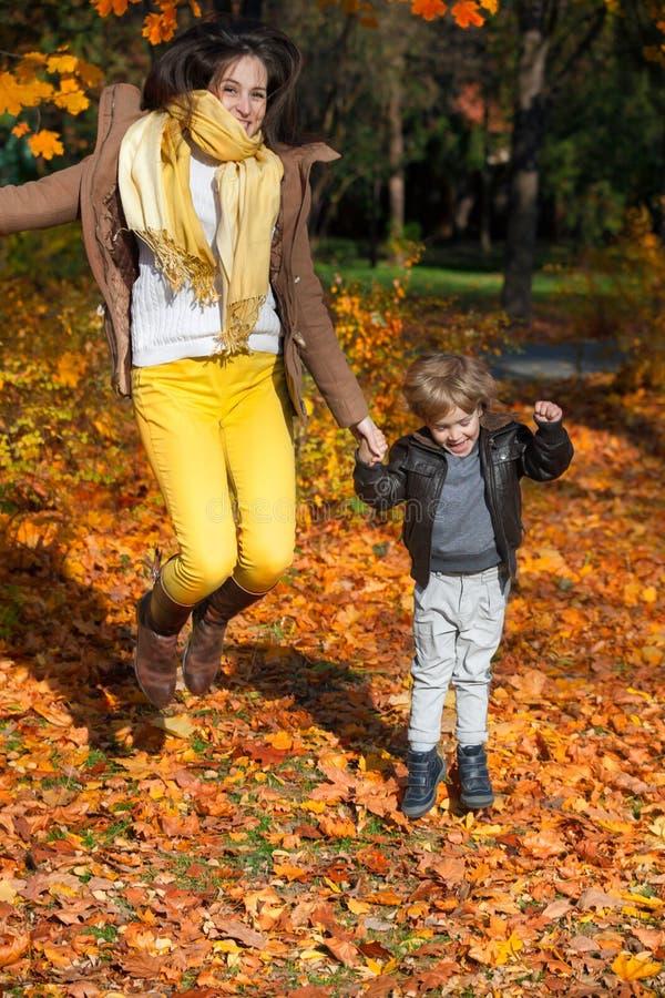 跳跃在公园的母亲和儿子 免版税库存图片