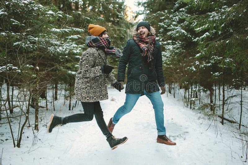跳跃在冬天森林里的年轻行家夫妇 免版税库存图片