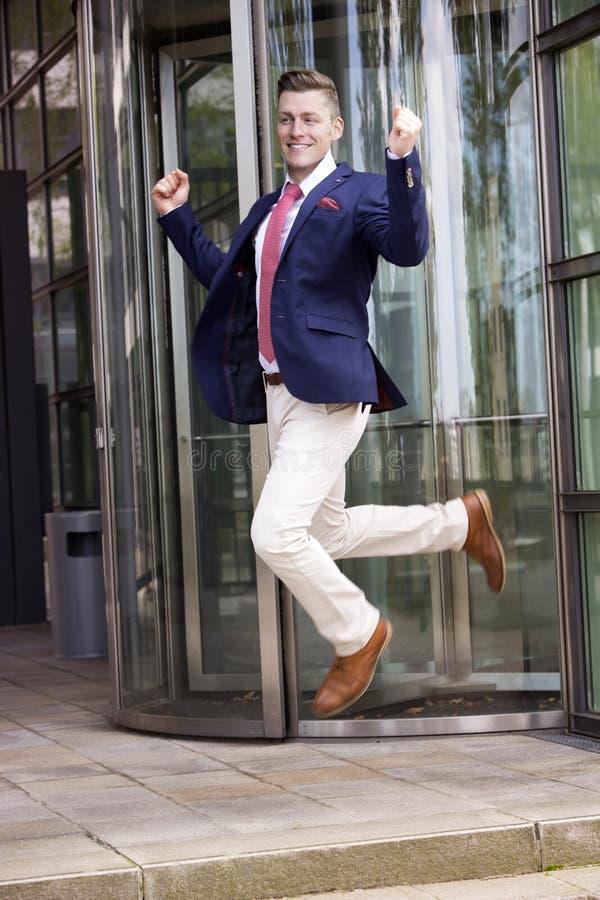 跳跃在办公楼前面的愉快的商人 图库摄影