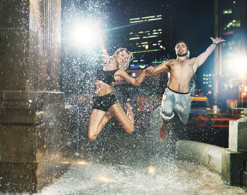 跳跃在喷泉的适合的夫妇 库存图片