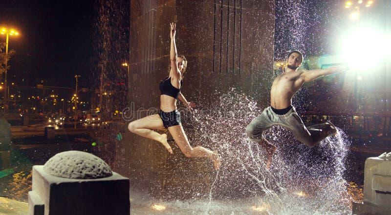 跳跃在喷泉的Attractiveain运动员 免版税库存图片