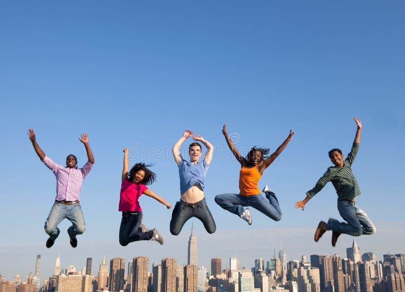 跳跃在城市的小组多种族人民 库存照片