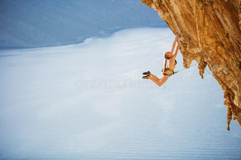 跳跃在复杂的路线的把柄的女性攀岩运动员在峭壁 免版税库存图片