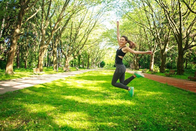 跳跃在夏天公园的嬉戏年轻健身妇女 库存照片