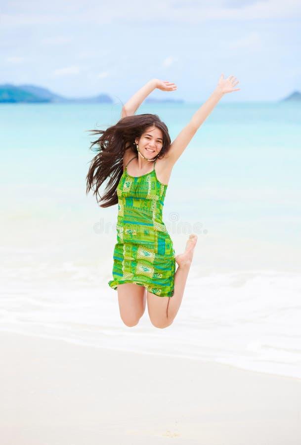 跳跃在夏威夷海滩的空气的美丽的两种人种的青少年的女孩 免版税库存图片