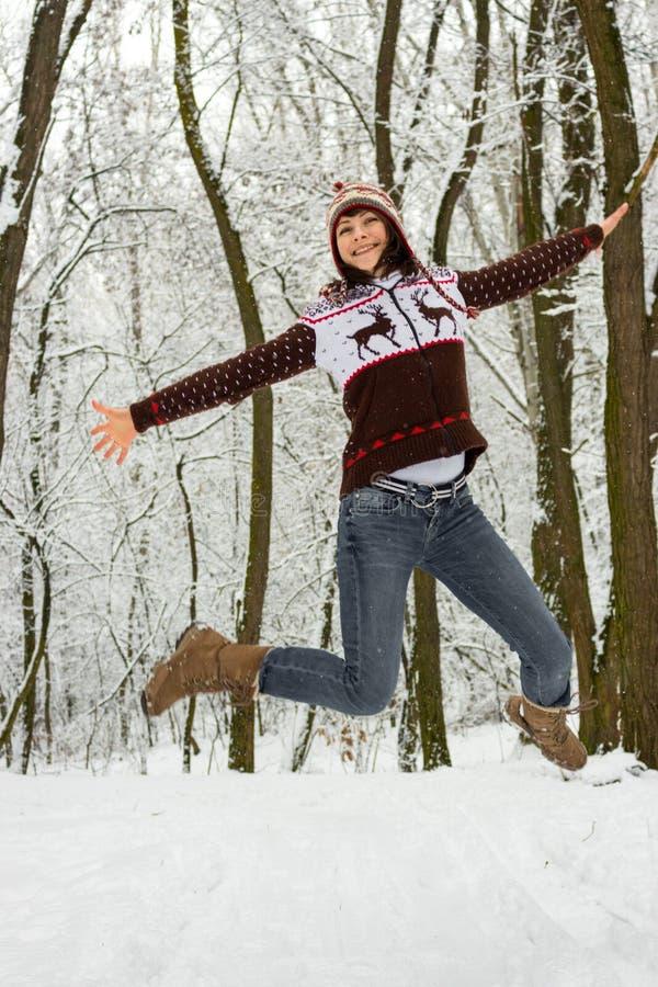 跳跃在多雪的冬天森林圣诞节背景中的被编织的舒适穿戴的愉快的女孩 有吸引力的冬天风景 跳的妇女 库存照片