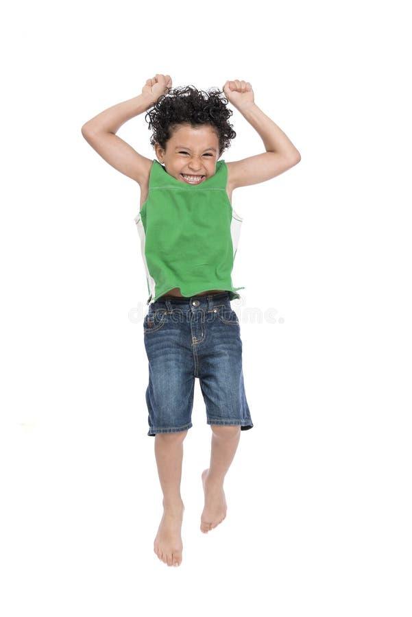 跳跃在天空中的一个年轻活跃愉快的男孩 免版税库存照片