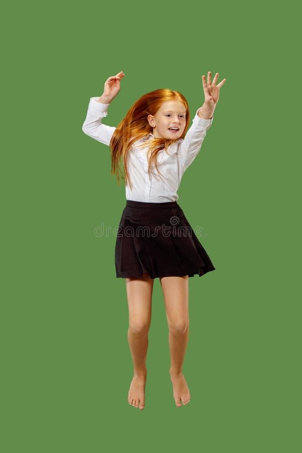 跳跃在天空中的年轻愉快的白种人青少年的女孩,隔绝在绿色背景 免版税库存图片