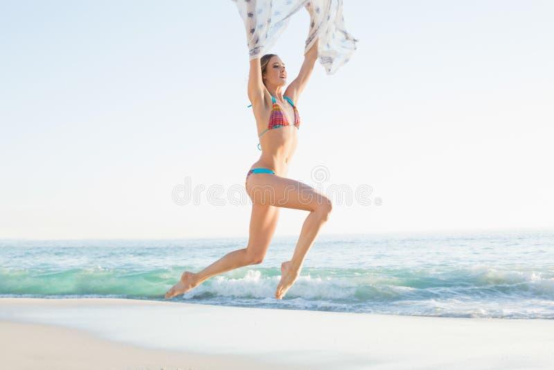 跳跃在天空中的快乐的苗条妇女拿着披肩 库存照片