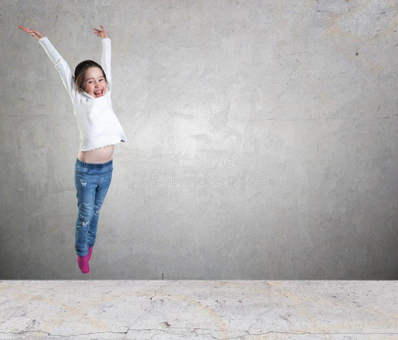 跳跃在天空中的愉快的小女孩反对混凝土墙背景 免版税库存照片