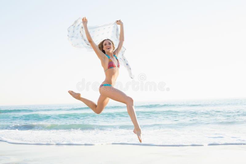 跳跃在天空中的愉快的苗条妇女拿着披肩 免版税库存照片