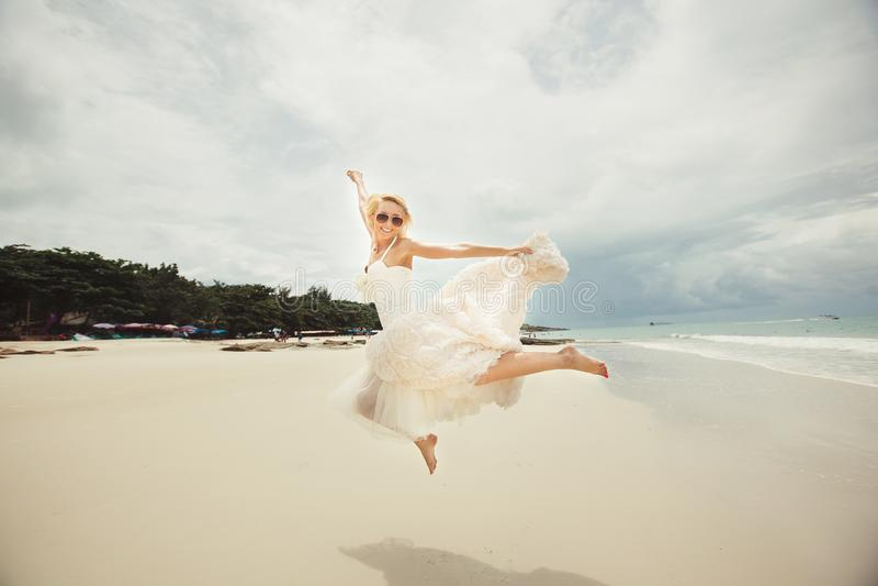 跳跃在婚礼礼服的愉快的新娘在海 海滩的年轻愉快的妇女 图库摄影