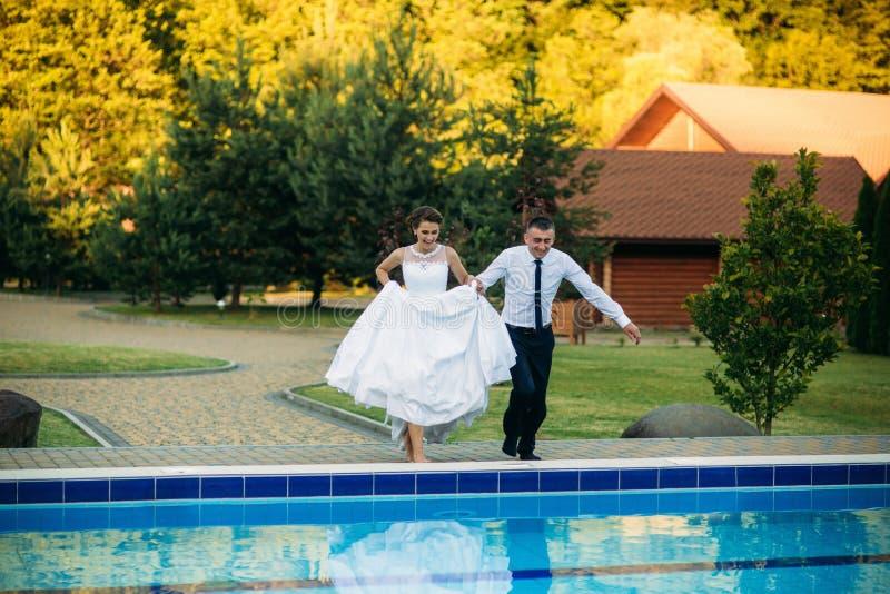 跳跃在婚礼衣服和婚礼礼服的游泳池的年轻夫妇 晴朗的日 库存照片