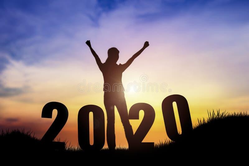 跳跃在小山的年轻女人剪影与2020新年快乐 图库摄影
