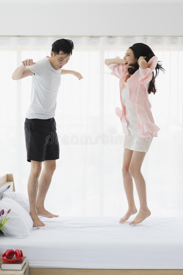 跳跃在床上的可爱的亚洲夫妇在卧室 免版税库存图片