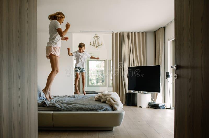 跳跃在床上的母亲和儿子 免版税库存图片