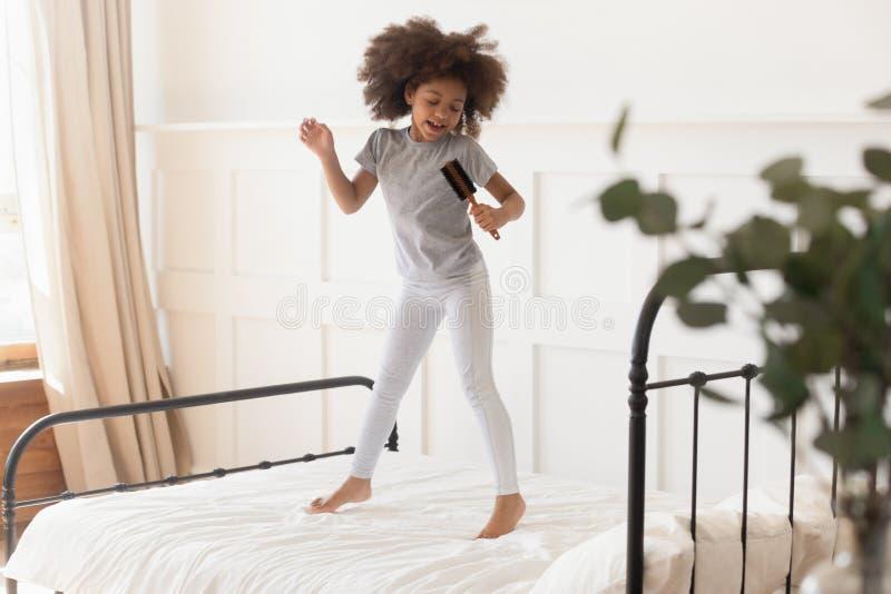 跳跃在床上的滑稽的非洲孩子女孩唱歌在发刷 免版税图库摄影